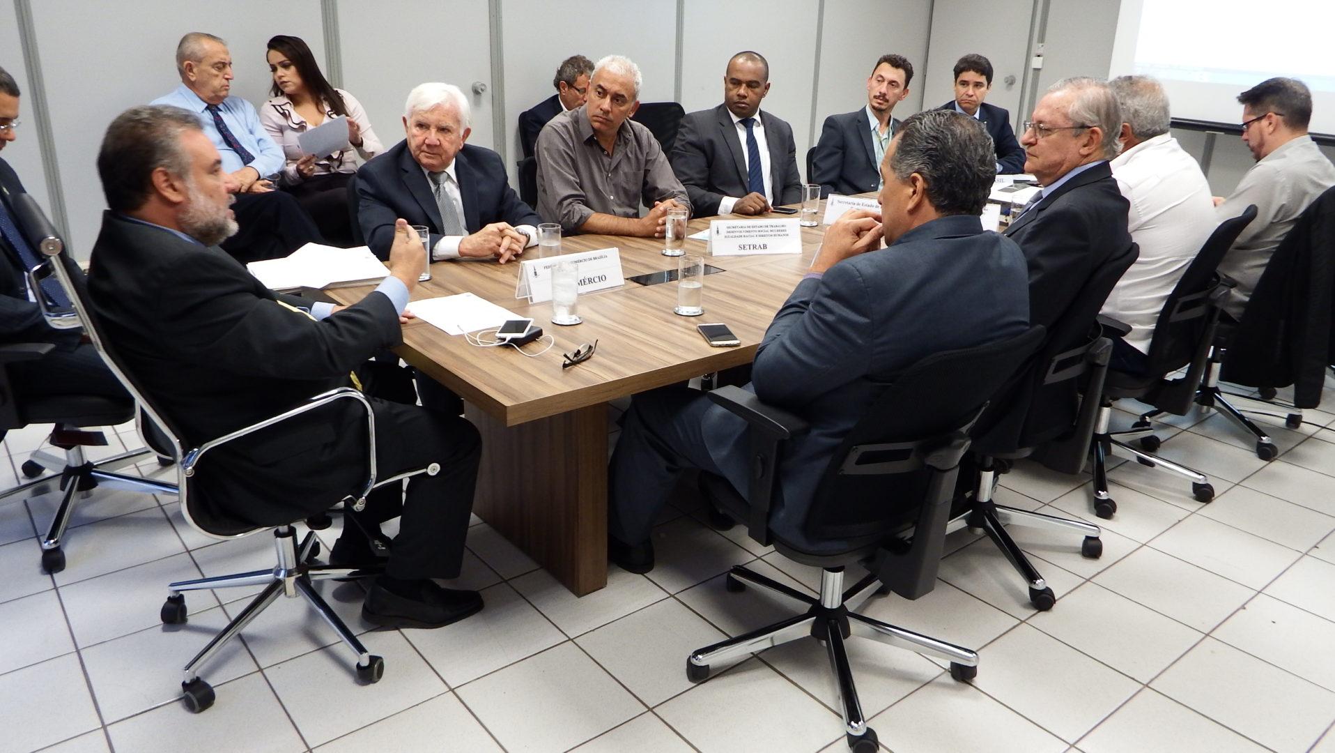 Secretario na pona da mesa reunido com conselhos para a provação de crédito